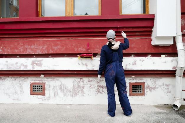 Mulher, reparador, carpinteiro, trabalhador em roupas de proteção, pinta as paredes do edifício. mãos femininas em luvas de proteção com rolo de pintura. o conceito de reparação profissional, restauração. Foto Premium