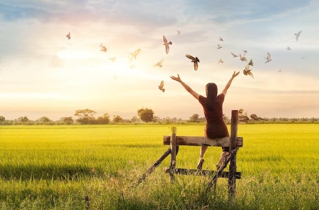 Mulher rezando e pássaro livre, apreciando a natureza no fundo por do sol, conceito de esperança Foto Premium