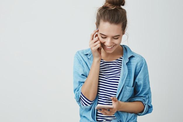 Mulher rindo sorrindo alegremente lendo mensagem fofa boba, digitando resposta pressionando a tela do smartphone, olhando a tela móvel divertido, alegre, tocando o rosto Foto gratuita