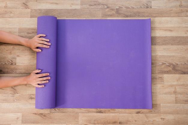 Mulher, rolando, esteira yoga Foto gratuita