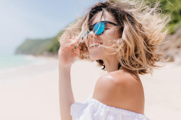 Mulher romântica de cabelos curtos com lindo sorriso posando em borrão natureza. mulher bronzeada encantadora em óculos de sol, rindo enquanto descansava na praia exótica. Foto gratuita