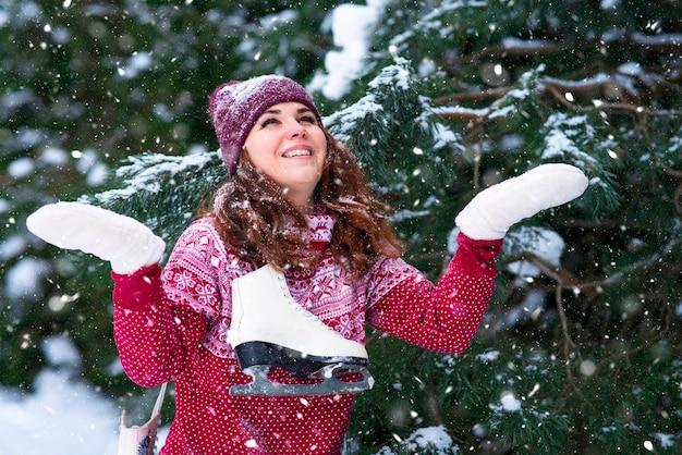 Mulher romântica segurando patins de inverno no ombro. diversão e esportes de inverno. menina pegando flocos de neve na floresta de inverno Foto Premium