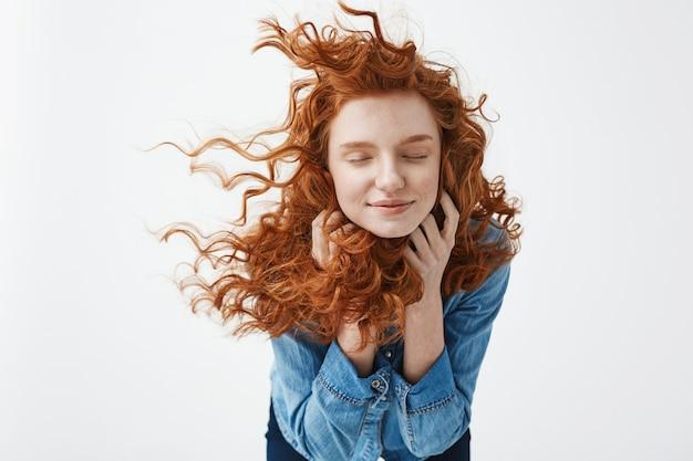 Mulher ruiva alegre com cabelo encaracolado a voar sorrindo rindo com os olhos fechados. Foto gratuita