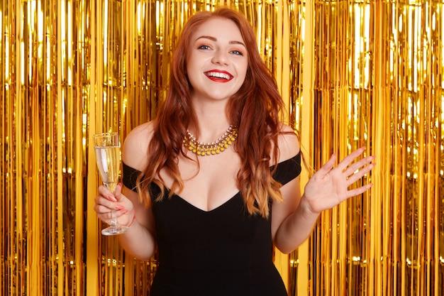 Mulher ruiva animada com as mãos estendidas de lado, segurando uma taça de vinho, comemorando o ano novo, em pé contra a parede amarela com glitter dourado. Foto gratuita