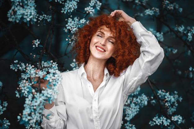 Mulher ruiva bonita em um jardim florescendo Foto Premium
