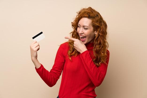 Mulher ruiva com camisola de gola alta segurando um cartão de crédito Foto Premium