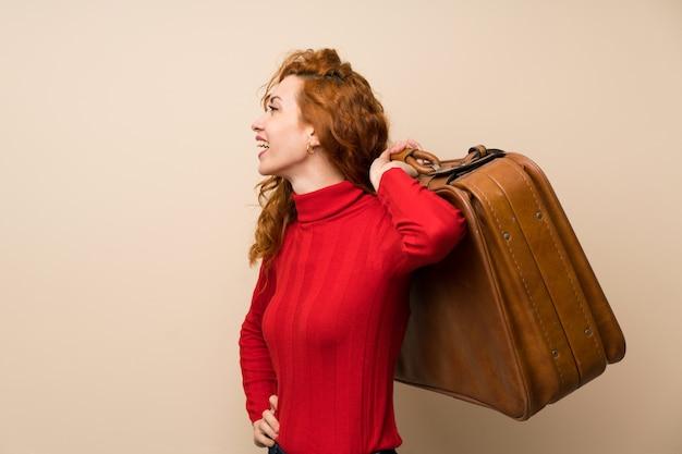 Mulher ruiva com camisola de gola alta segurando uma maleta vintage Foto Premium