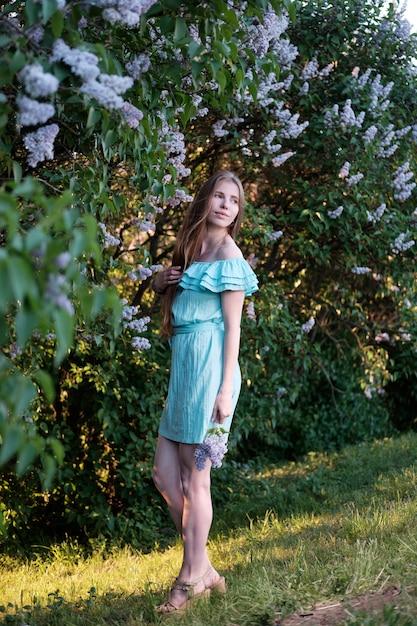 Mulher ruiva em vestido de cocktail azul claro em arbustos lilás Foto Premium