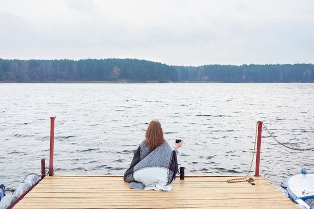 Mulher ruiva, embrulhada em um cobertor xadrez, sentada no píer do lago e tomando café da garrafa térmica Foto Premium