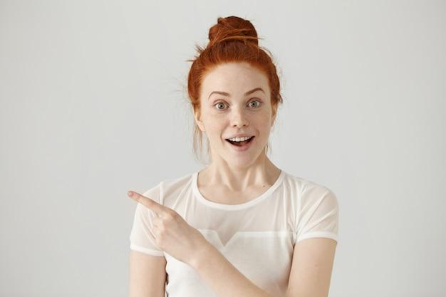 Mulher ruiva jovem animado com nó de cabelo, apontando o dedo indicador para os lados, levantando as sobrancelhas e mantendo a boca aberta, mostrando algo surpreendente Foto gratuita