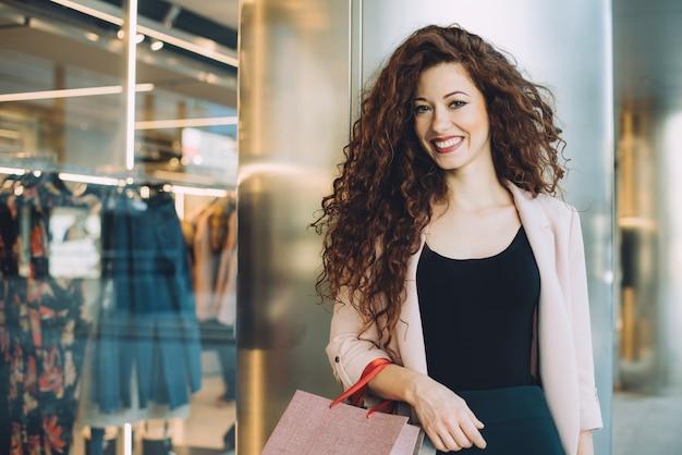 Mulher ruiva jovem bonita feliz fazendo compras Foto Premium