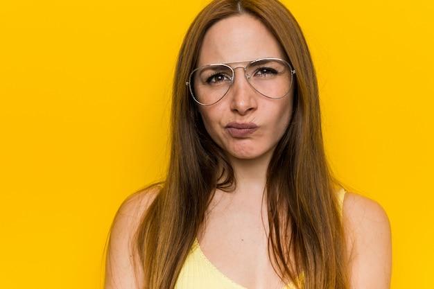 Mulher ruiva jovem ruiva com rosto sardento freckless em desagrado, mantém os braços cruzados. Foto Premium