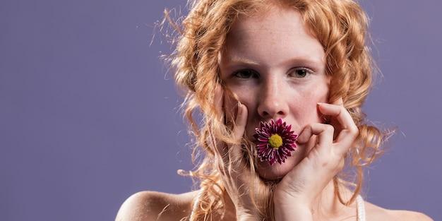 Mulher ruiva posando com um crisântemo na boca e cópia espaço Foto gratuita