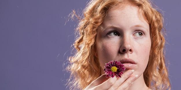 Mulher ruiva segurando uma flor perto da boca com espaço de cópia Foto gratuita