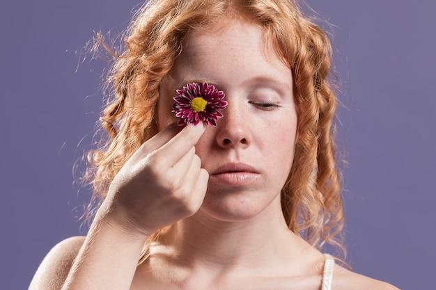 Mulher ruiva segurando uma flor sobre o olho dela Foto gratuita