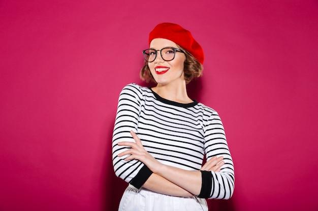 Mulher ruiva sorridente em óculos posando com braços cruzados e olhando para a câmera sobre rosa Foto gratuita