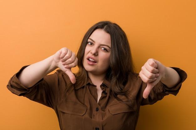 Mulher russa curvilínea jovem mostrando o polegar para baixo e expressando antipatia. Foto Premium