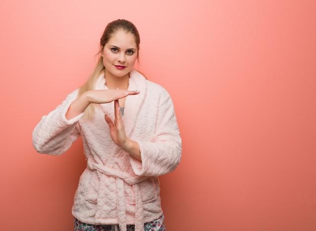 Mulher russian nova que desgasta o pyjama que faz um gesto do timeout Foto Premium
