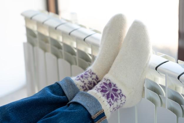Mulher se aquecendo com os pés no aquecedor usando meias de lã Foto Premium