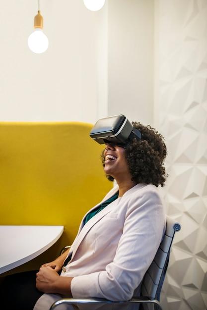Mulher se divertindo com um fone de ouvido de realidade virtual Foto gratuita