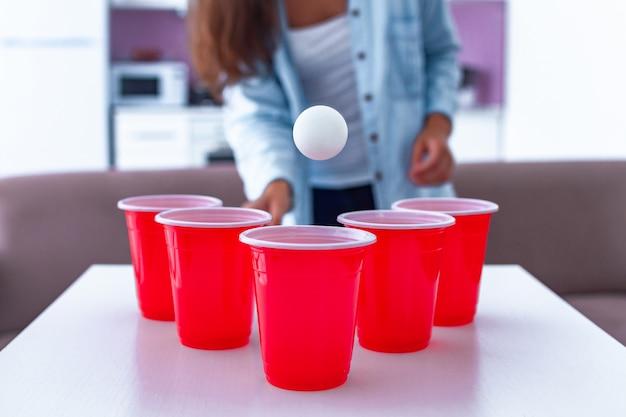 Mulher se divertindo e curtindo o jogo de pong de cerveja na mesa em casa Foto Premium