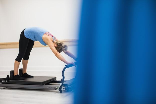 Mulher se exercitando no reformador Foto gratuita