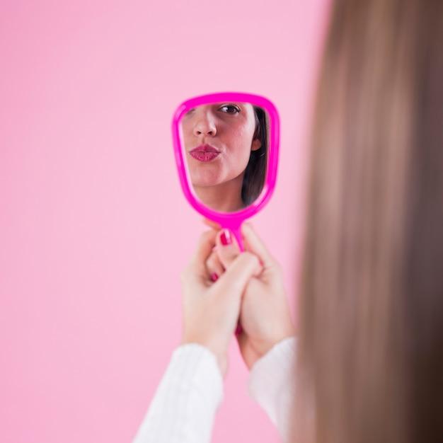 Mulher se olhando no espelho e mandando beijo Foto gratuita