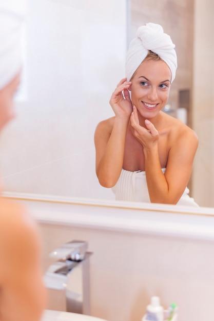 Mulher se olhando refletida no espelho após o banho Foto gratuita