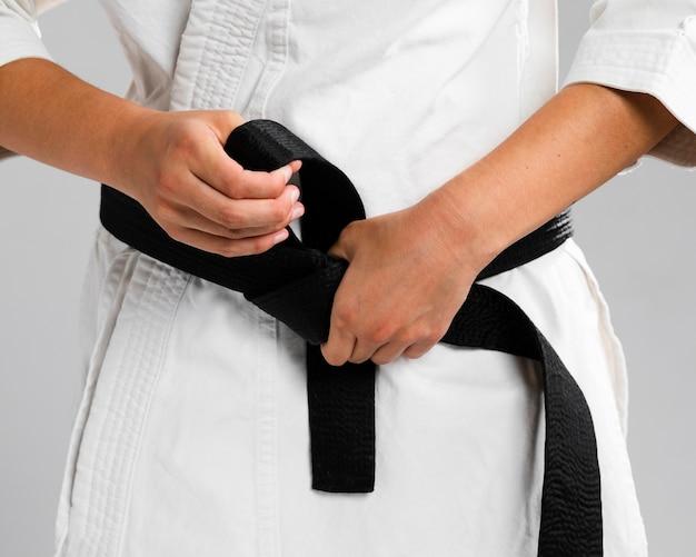 Mulher se vestindo de uniforme e faixa preta Foto gratuita