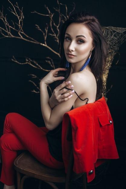 a9fecd7a67dc Mulher sedutora em traje vermelho senta-se diante de uma árvore brilhante  Foto gratuita