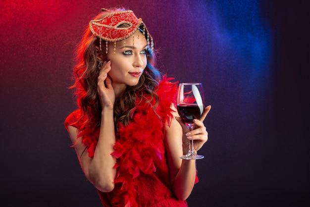 Mulher sedutora em uma máscara de carnaval vermelho e boa com um copo de vinho levantado olhando para longe Foto Premium