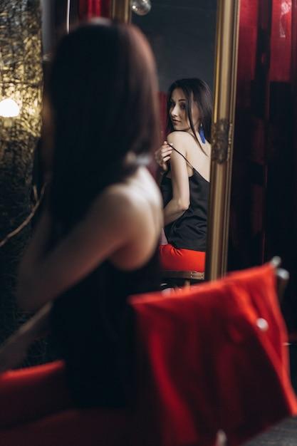 Mulher sedutora tira a roupa sentada diante de um espelho Foto gratuita