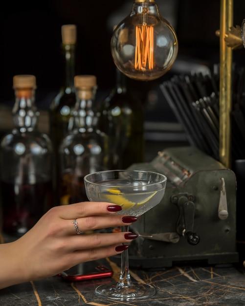 Mulher segura álcool beber guarnecido com casca de limão no copo de martini Foto gratuita