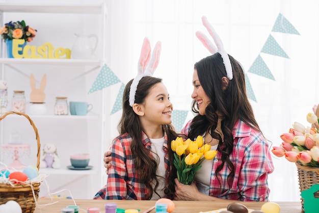 Mulher segura, amarela, tulips, buquê, abraçar, dela, filha, ligado, dia páscoa, celebração Foto gratuita