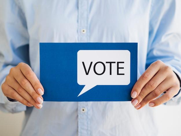 Mulher segura, azul, cartão, com, voto, fala, bolha Foto gratuita