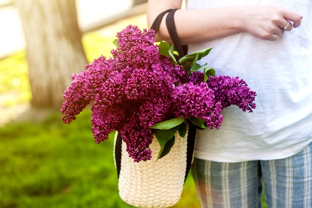 Mulher segura, bolsa palha, com, vívido, grupo, de, lilás, flores Foto Premium
