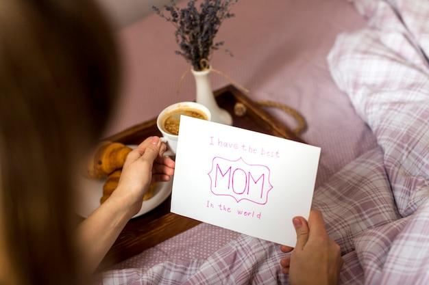 Mulher segura, cartão cumprimento, e, xícara café, ligado, bandeja Foto gratuita