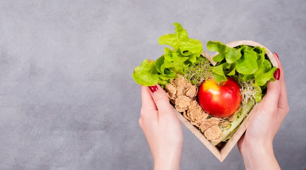 Mulher segura, coração madeira, com, maçã, e, cereais Foto gratuita