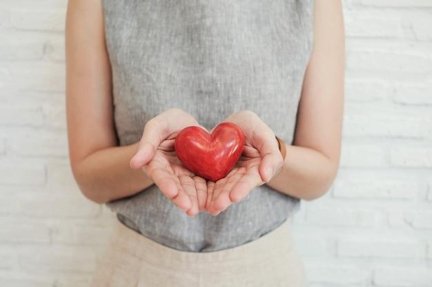 Mulher segura, coração vermelho, seguro saúde, doação, caridade, conceito Foto Premium