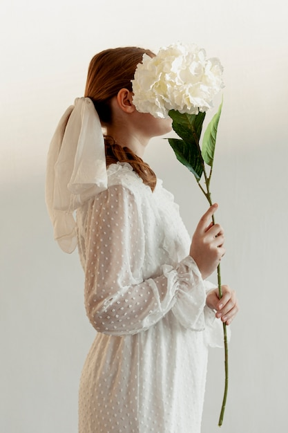 Mulher segura, flor, vista lateral Foto gratuita