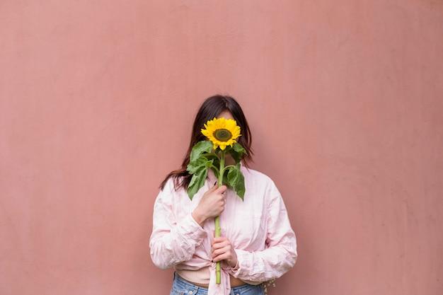 Mulher segura, fresco, flor amarela, perto, rosto Foto gratuita