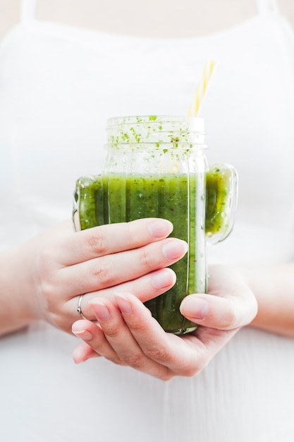 Mulher segura, garrafa, de, smoothie verde Foto gratuita