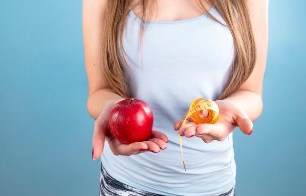Mulher segura, maçã vermelha, com, medindo fita, em, mãos Foto gratuita