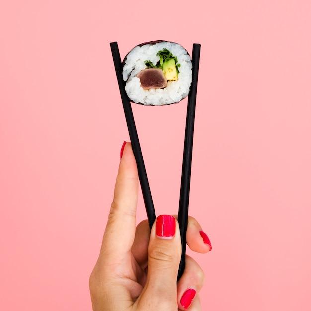 Mulher segura, pauzinhos, com, rolo sushi Foto gratuita