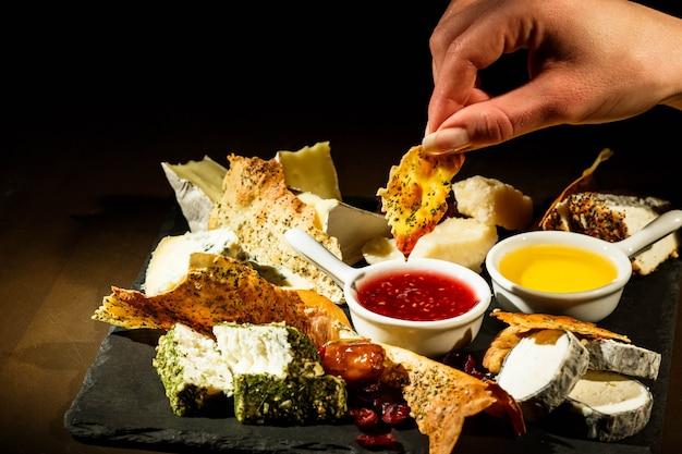 Mulher, segura, pedaço, queijo, sobre, tigela, cranberry, molho Foto gratuita