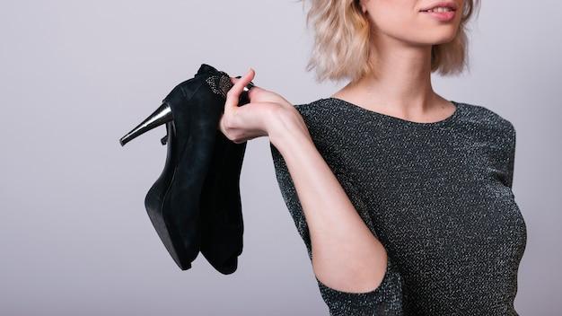Mulher segura, sapatos, em, mão Foto gratuita