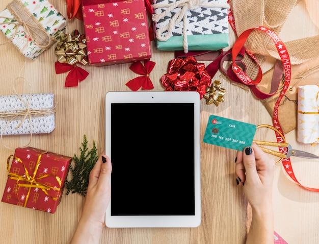 Mulher segura, tabuleta, e, cartão crédito, em, tabela Foto gratuita