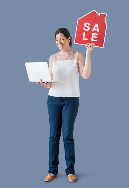 Mulher segura, um, casa, venda, ícone, e, um, laptop Foto gratuita