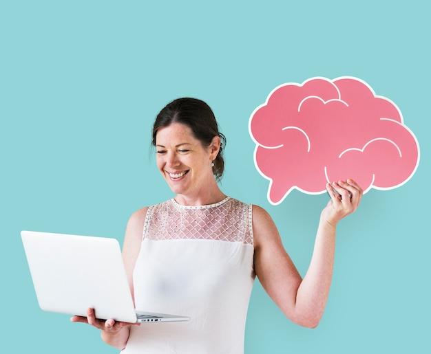 Mulher segura, um, cérebro, ícone, e, usando, um, laptop Foto gratuita