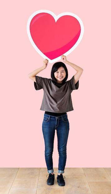 Mulher segura, um, coração, emoticon, em, um, estúdio Foto gratuita